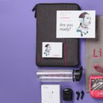 Collection of branded merchandise products such as tote bags and water bottles against purple backdrop.