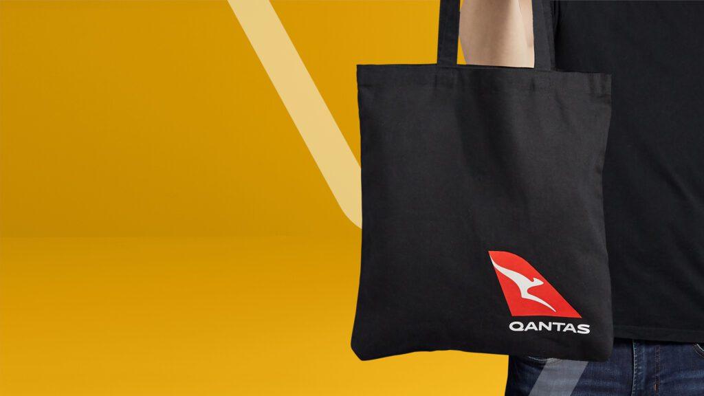 Black branded tote bag being held by person with Qantas airways branding on bag.