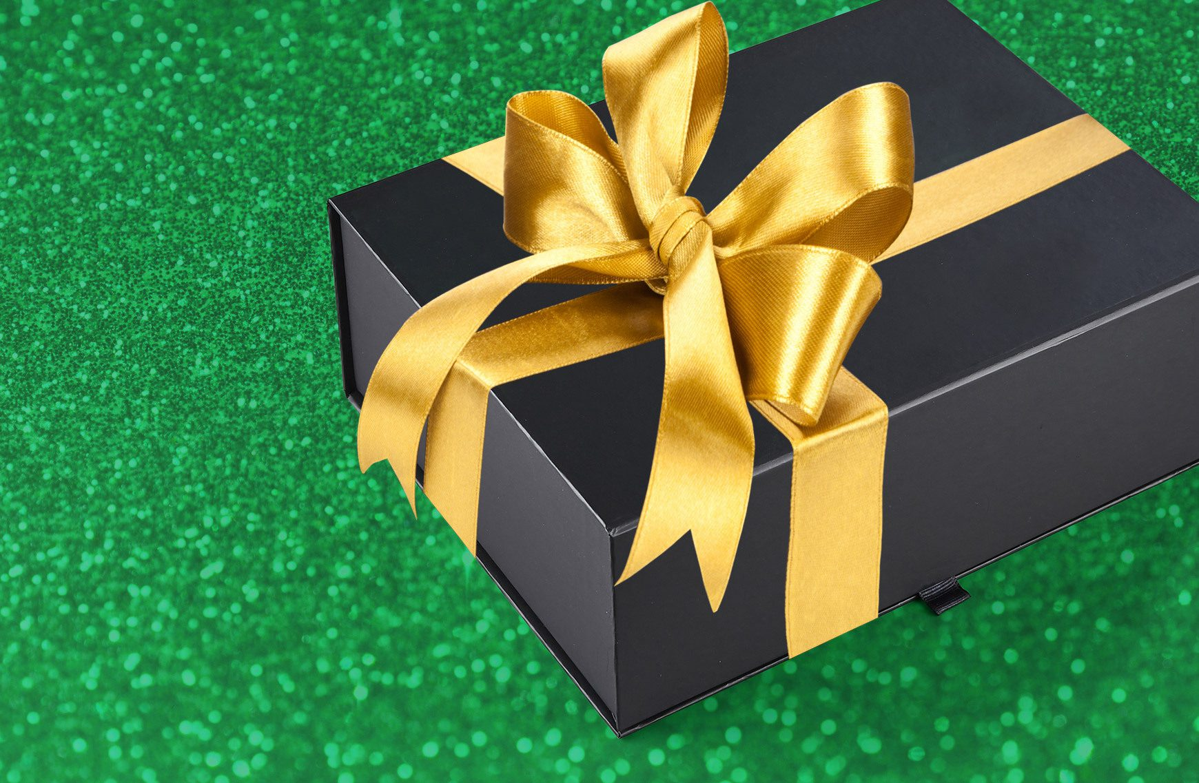 Black box wrapped with gold bow on sparkly green background