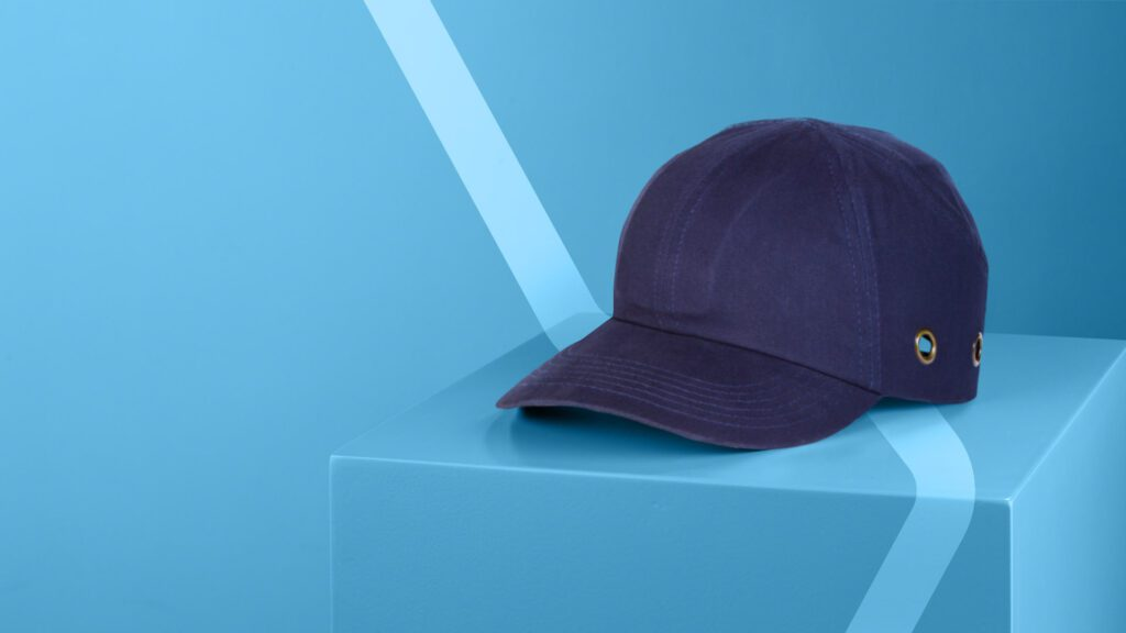 Navy branded bump cap on plinth