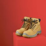 Workboots on plinth against red background