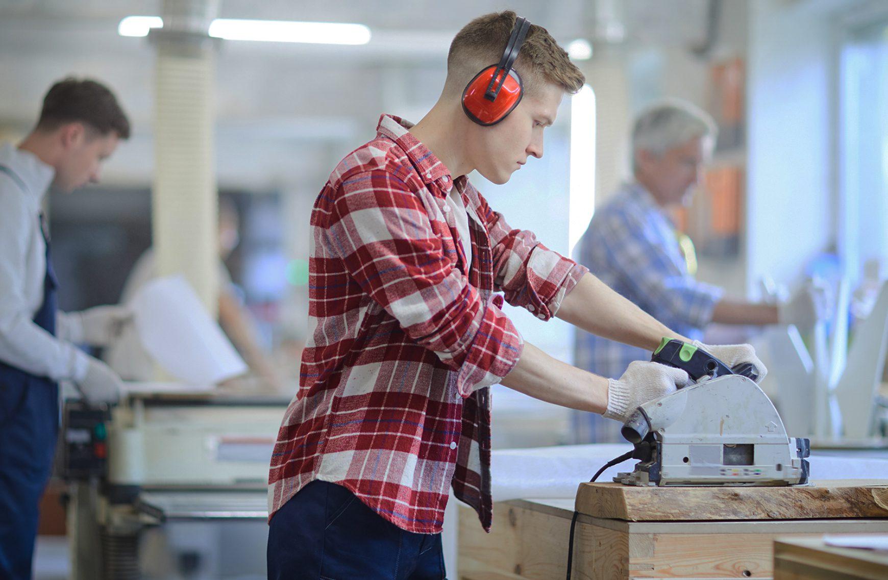 Man working at machine wearing ear defenders