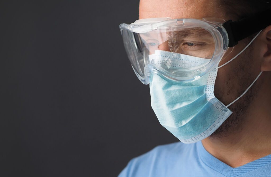 Man wearing ppe goggles and face mask