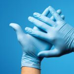 Hands wearing nitrile vinyl gloves against plain blue background