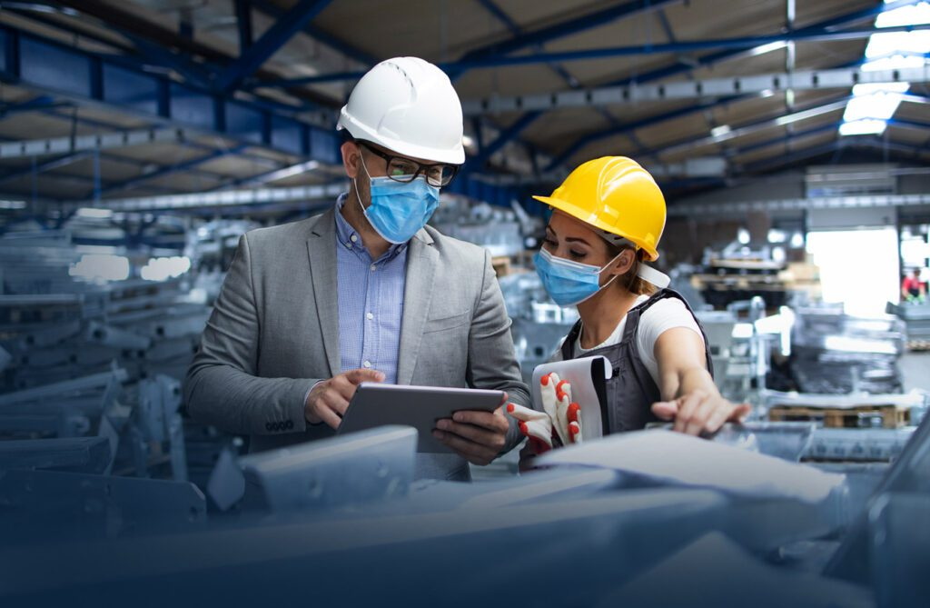Image of two workers in factory wearing hard hats looking for ways to improve health and safety in the workplace
